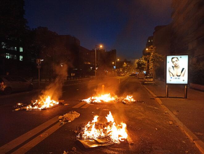 Feux devant un panneau marchandisant le corps de la femme, suite au rassemblement (interdit) devant le tribunal de Paris en mémoire du corps supplicié d'Adama Traoré en 2016, la manifestation du 2 juin 2020 reprend le slogan « je ne peux pas respirer » une semaine après la mort de George Floyd mort également par asphyxie lors d'une intervention policière © Hugues Bazin