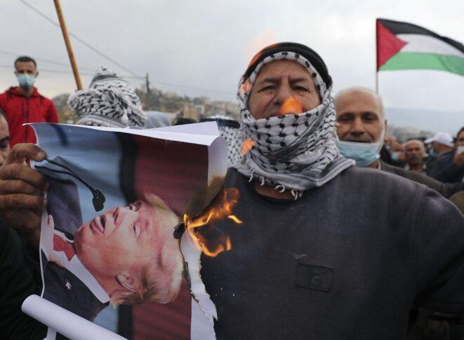 Des manifestants palestiniens brûlent des portraits de Donald Trump en Cisjordanie, le 6 novembre 2020. © Abbas Momani/AFP