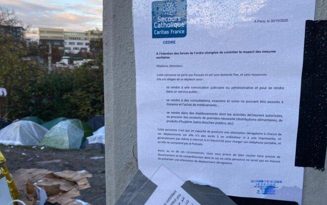 L'association Secours Catholique affiche une lettre sur le mur de l'autoroute A devant les tentes. © Mortaza Behboudi
