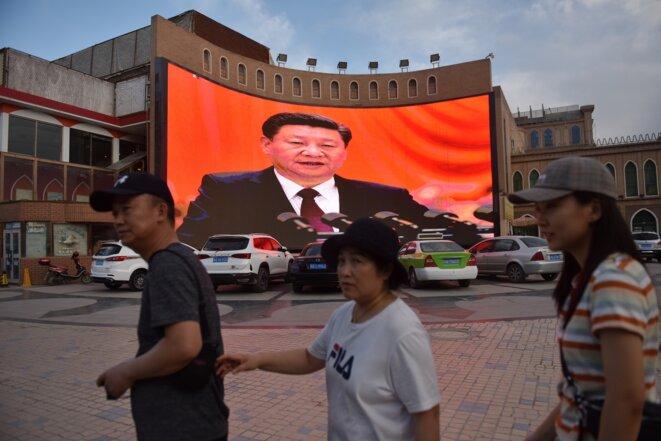 Des passants devant un écran montrant le président chinois Xi Jinping à Kachgar, ville de la région autonome ouïghoure du Xinjiang, en juin 2019. © Greg Baker / AFP