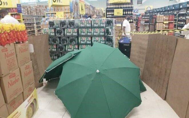 Corps d'un employé décédé dans le magasin, masqué par des parasols;