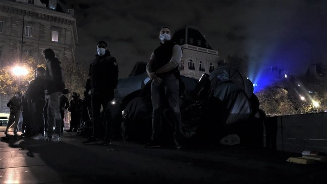 Des agents de la BAC en civil gardent un tas de tentes confisqué aux exilé.e.s sur la Place de la République © Emile Rabreau