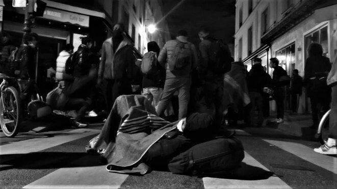 Un homme exilé se repose lors de l'attente dans la rue des Archives © Emile Rabreau