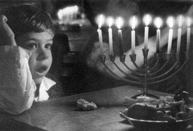 Un enfant devant une hanoukkia brillant de tous ses feux à Zot Hanoucca (8e jour). © Domaine Public