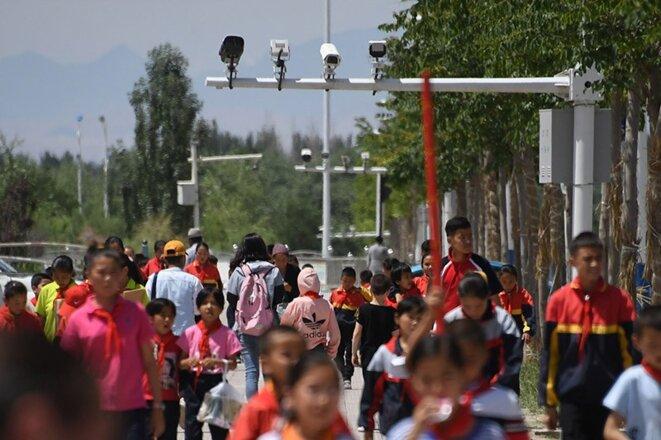 Des écoliers marchent sous les caméras de surveillance dans le Xinjiang, dans l'ouest de la Chine.Crédit: Greg Baker / AFP / Getty