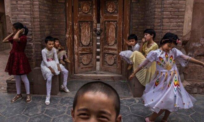 Des enfants ouïghours sont assis devant une mosquée à Kashgar en juin 2017 après sa fermeture par les autorités chinoises. Photographie : Kevin Frayer/Getty Images