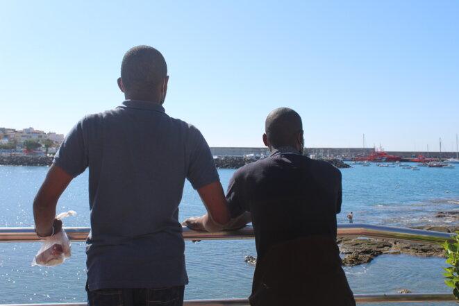Deux migrants subsahariens observant le port d'Arguineguin, où ils ont débarqué en novembre 2020. © NB.