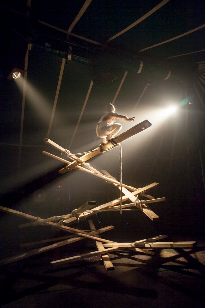 Johann Le Guillerm s'élève sur une hélice de planches qu'il construit au fur et à mesure de son ascension. Spectacle Secret(temps2), 2019. Photographie David Dubost. © Photographie David Dubost.