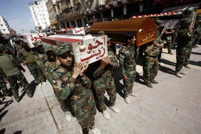 A Nadjaf (Irak) en mars 2016, des hommes de la milice chiite Asaïb Ahl al-Haq portant les cercueils de camarades tombés en Syrie. © Haidar Hamdani/AFP