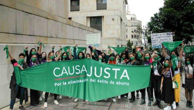 """Bogota, 2020. Des militantes féministes brandissent le foulard vert devant le Palais de Justice, siège de la Cour Constitutionnelle qui doit examiner une """"tutela"""" pour l'IVG. © Movimiento Causa Justa"""