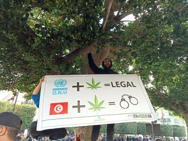 Un manifestant brandit une banderole contre la criminalisation du cannabis. © Aymen Rezgui