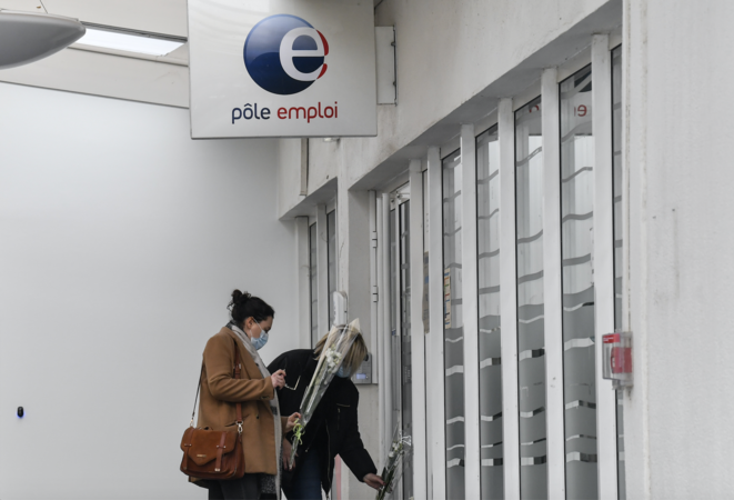 Two women lay flowers at the Pôle Emploi branch in Valence on January 29th 2021, a day after the murder of a supervisor there. © PHILIPPE DESMAZES / AFP