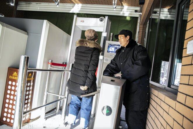 Un agent de sécurité observe le passage d'une femme à un point de contrôle, équipé d'un détecteur de métaux et d'une technologie de reconnaissance faciale, pour entrer dans le bazar principal d'Ürümqi, dans le Xinjiang, le 6 novembre 2018. Photo: Bloomberg via Getty Images