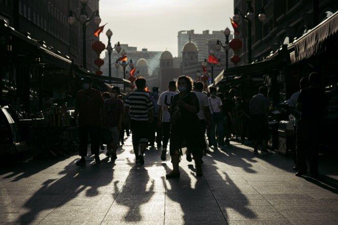 Des gens marchent dans la rue du Grand Bazar international du Xinjiang, le 25 juin 2020 à Ürümqi. Photo: David Liu/Getty Images