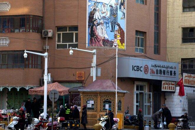 Des résidents passant devant un point de contrôle de sécurité et des caméras de surveillance dans une rue de Kashgar, Xinjiang, le 5 novembre 2017. Photo: Ng Han Guan / AP