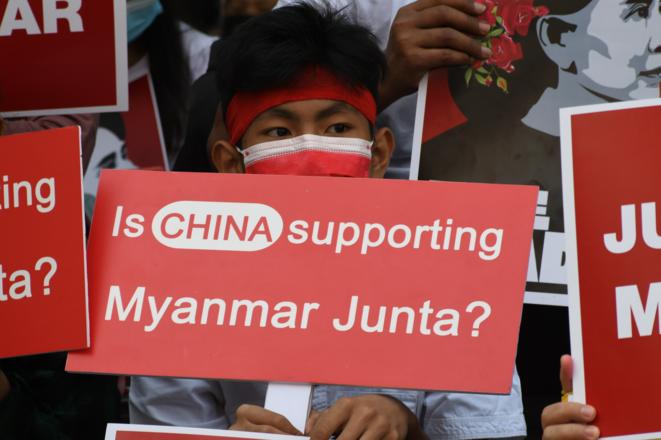 Dans le centre de Yangon, le 25 février 2021, un manifestant tient une banderole suggérant l'implication de la Chine dans le soutien au coup d'État au Myanmar. Le mouvement prodémocratie est enragé par le refus de la Chine et de la Russie de condamner ouvertement le coup d'État au Conseil de sécurité des Nations unies et dénonce l'influence régionale de la Chine au sein de l'Alliance du thé au lait. © Collectif The Myanmar Project
