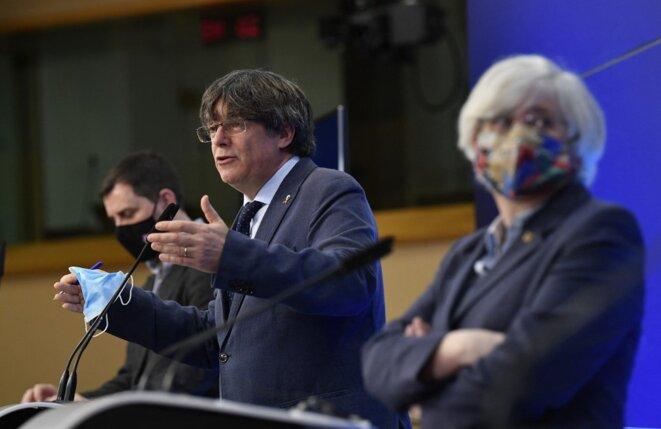 Carles Puigdemont, entouré de Toni Comín et Clara Ponsatí, lors d'une conférence de presse au Parlement européen le 24 février 2021 © AFP/John Thys.