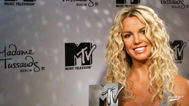 Britney Spears au moment de sa carrière, elle a les cheveux blonds et bouclés. Elle se tient devant un panneau avec les marques MTV et le musée de Madame Tussaud lors d'un festival