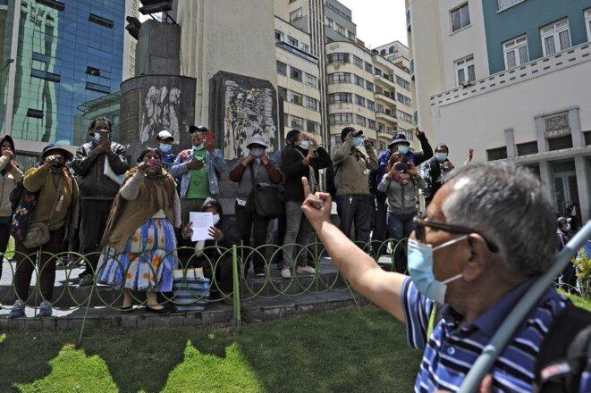 Un opposant au gouvernement de Luis Arce fait un doigt d'honneur à des partisans du Mouvement vers le Socialisme le 17 mars 2021 lors d'une manifestation à La Paz. © Jorge Bernal/AFP