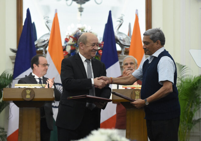 French defence minister Jean-Yves Le Drian (left) shakes hands with his Indian counterpart Manohar Parrikar in New Delhi on January 25th 2016 during a joint press conference with (behind) then French president François Hollande and Indian Prime Minister Narendra Modi applauding the deal. © Prakash Singh / AFP