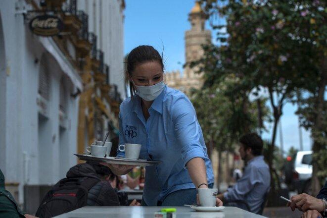 Une serveuse, le 11 mai 2020, à Séville. Le secteur de l'hôtellerie et de la restauration pourrait s'avérer l'un des plus rétifs à la semaine des quatre jours. © AFP / Cristina Quicler