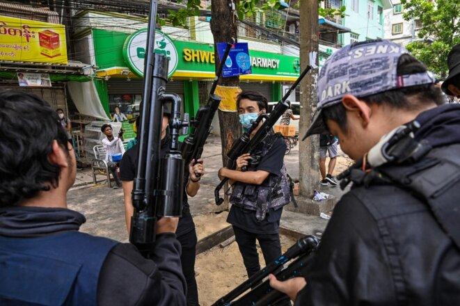 Dans la banlieue de Tamwe à Yangon, des protestataires exhibent leurs armes artisanales. © AFP