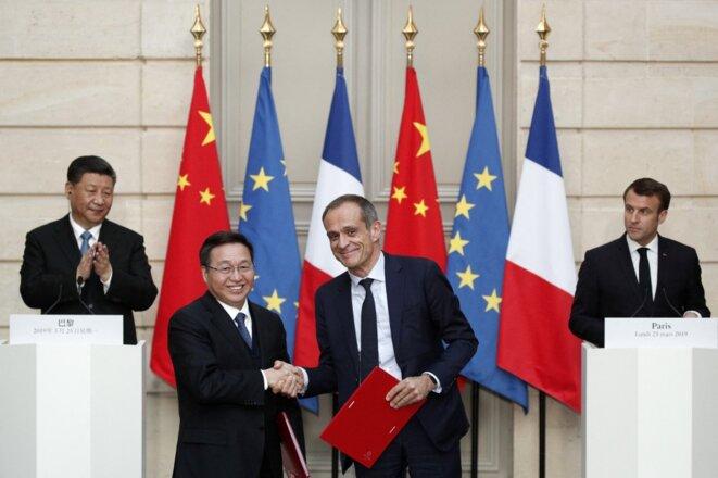25 mars 2019, palais de l'Elysée. Jean-Pascal Tricoire sert la main du président de la Banque de Chine, sous les regards de Xi Jinping et d'Emmanuel Macron. © Yoan Valat/AFP.