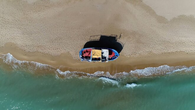 A stranded boat for migrants on a Southern Mediterranean Sea beach © GLF Media - Shutterstock