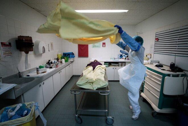 Le 29 janvier 2021, à la morgue de l'hôpital Bichat, à Paris, un membre de l'équipe médicale drape le corps d'un défunt, juste avant l'arrivée de proches. © Joel Saget / AFP