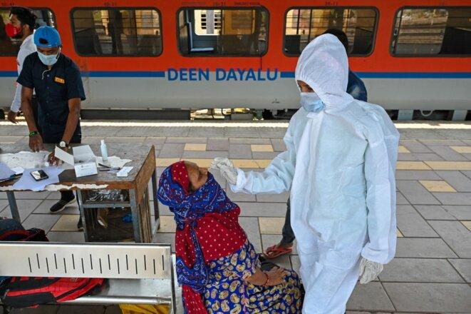 Une passagère testée à son arrivée à la gare de Bombay, le 14 avril 2021. © Punit Paranjpe/AFP