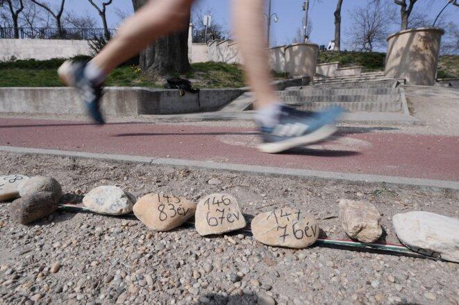 Un joggeur court devant quelques-uns des 20 000 cailloux alignés le long de la route pour commémorer les victimes du coronavirus en Hongrie, le 2 avril 2021 sur l'île Margaret à Budapest. © Attila Kisbenedek/AFP