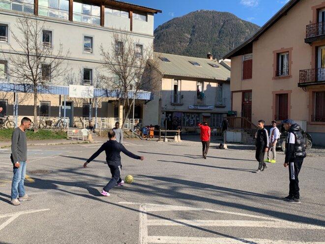 Des jeunes jouant au football devant l'entrée du refuge solidaire à Briançon. © NB