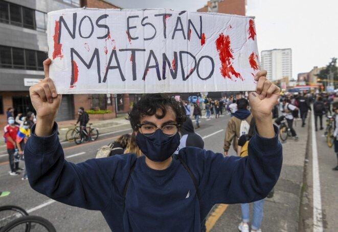 Un manifestant brandit une pancarte « Ils nous tuent » à Bogota le 4 mai 2021. © Juan Barreto/AFP