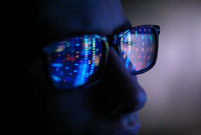 Reflet de l'écran d'ordinateur dans les lunettes du profil ADN, gros plan du visage. © Andrew Brookes / Getty Images