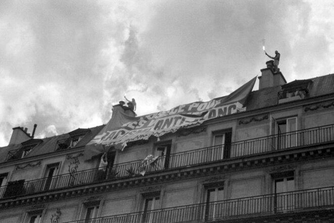 """Banderole """"Justice pour les victimes du racisme anti-blanc """" des militant·e·s du collectif Génération Identitaire sur le toit de l'immeuble au croisement de la rue du Temple et de la rue Béranger, Paris, le 13 juillet 2020. © Éris"""