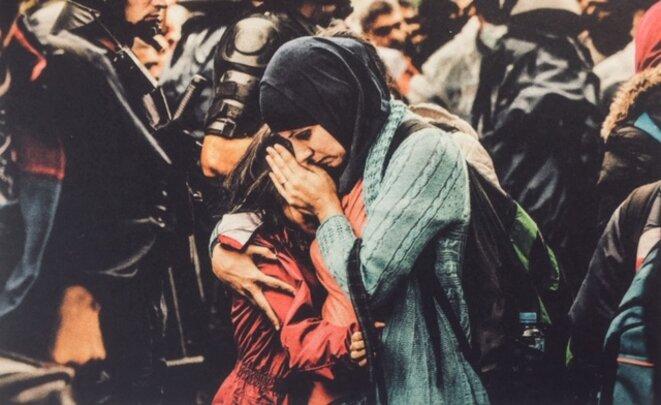 « Tovarnik, Croatie, septembre 2015 Une mère couvre le visage de sa fille, dans la confusion d'une foule de réfugiés qui attendent d'être conduits en car vers l'Europe centrale » © Carlos Spottorno - 'En mer, pas de taxis'