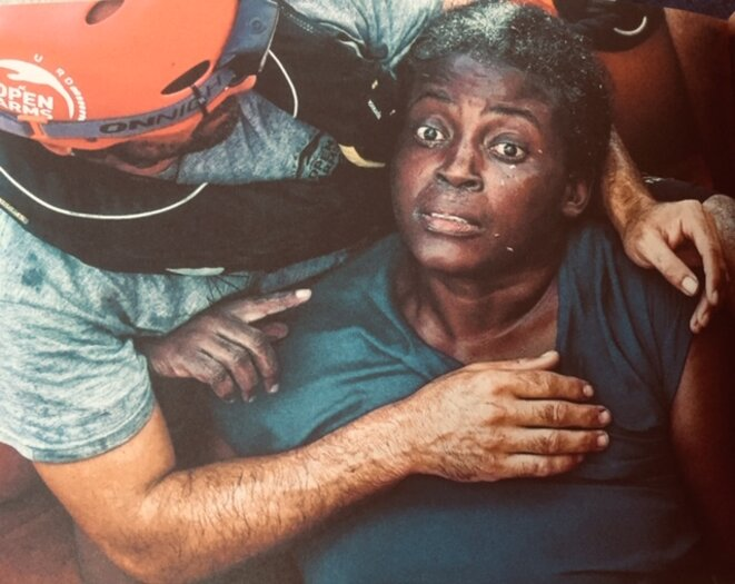 « Méditerranée centrale, le 17 juillet 2018. Un membre de l'équipage du navire de l'ONG Proactiva Open Arms serre dans ses bras Joséfa, originaire du Cameroun; elle a été portée à bord dans un état de choc profond, après une nuit passée à s'accrocher à l'épave, à chanter des hymnes religieux et à en appeler à Dieu. » © Juan Medina - 'En mer, pas de taxis'