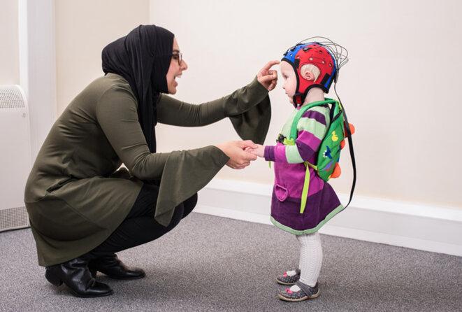 Une femme parle à son enfant dans un casque EEG © Avec l'aimable autorisation d'Emily Jones