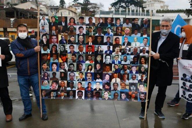 Des membres de la communauté ouïghoure de Turquie tiennent une pancarte montrant des Ouïghours, qu'on craint être détenus dans des camps du Xinjiang, devant le consulat de Chine à Istanbul en février.  Crédit: AP