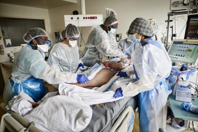 Des soignants prennent en charge un patient atteint du Covid-19 dans le service de réanimation de l'Institut mutualiste Montsouris à Paris. © Antonin Burat / Hans Lucas via AFP