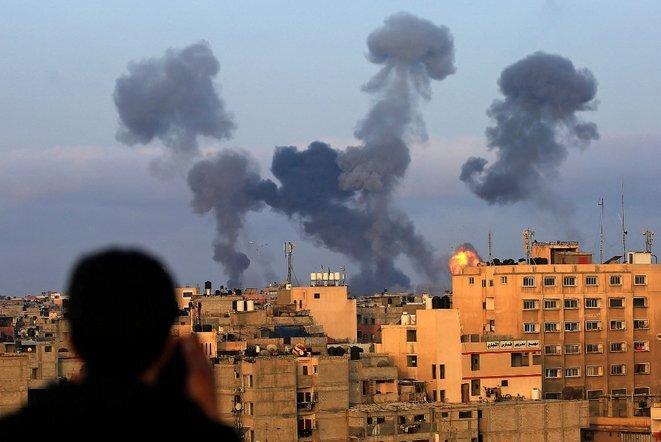 Un niño palestino mira el humo que sale de la región sur de Gaza tras los ataques israelíes. © Mahmoud Khatab/AFP