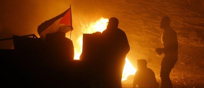 Des Palestiniens et leur drapeau lors d'un rassemblement anti-israélien au checkpoint de Qalandiya, le 11 mai 2021. ABBAS MOMANI / AFP
