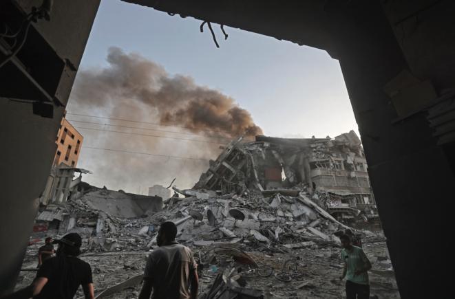 Au milieu des décombres devant la tour Al-Sharouk effondrée après une frappe aérienne israélienne, dans la ville de Gaza, le 12 mai 2021. © Mohammed ABED / AFP