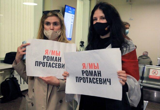"""""""Je suis, nous sommes Roman Protasevich"""". Deux femmes brandissent cette inscription à Vilnius le 23 mai 2021 à l'arrivée de l'avion. © Petras Malukas/AFP"""