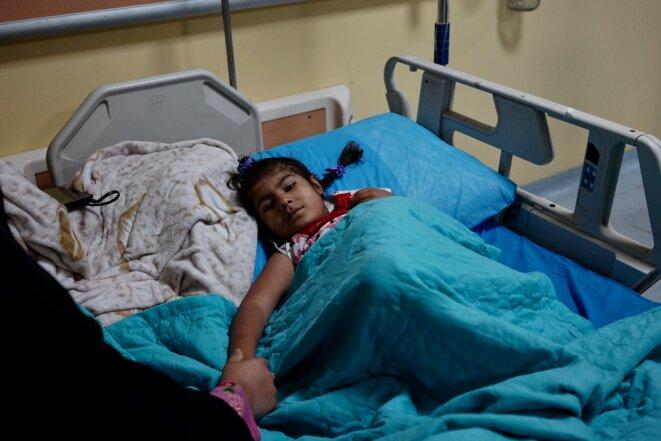 Ilaf, 5 ans, née polydactyle et sans anus, tient la main de sa mère dans son lit d'hôpital (Bassorah, avril 2021) © Rachida El Azzouzi