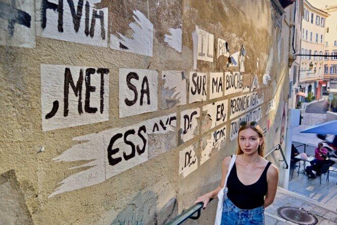 La militante Anaïs Mattei devant un collage féministe dans le centre de Bastia. © CM / Mediapart