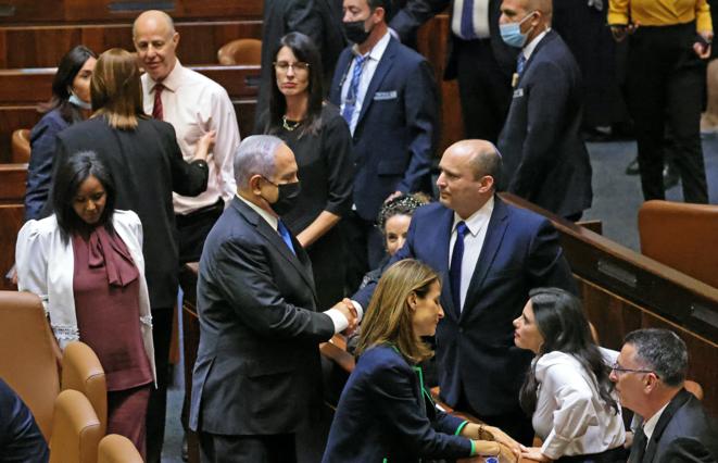 """Benyamin Netanyahu felicita a su sucesor, el nuevo primer ministro Naftali Bennett, tras la votación que consagró la coalición """"anti-Bibi"""" en la Knesset, el 13 de junio de 2021. © EMMANUEL DUNAND/AFP"""