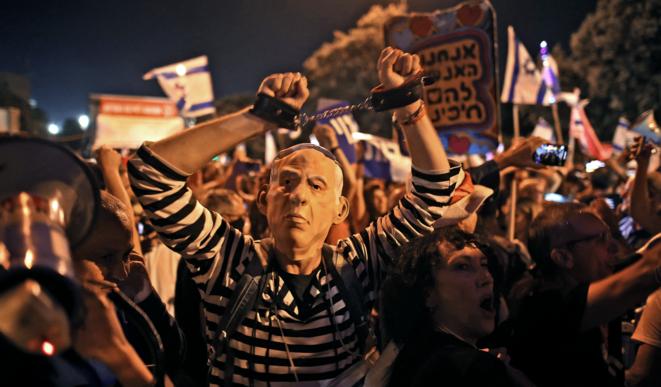 """Frente a la Knesset, manifestantes anti-Netanyahu celebran el fin del reinado del primer ministro israelí, derrotado por una coalición """"anti-Bibi"""", el 13 de junio de 2021. © Ahmad Gharabli/AFP"""