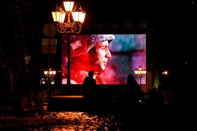 Sur un écran géant d'Erevan le 5 octobre 2020 est diffusée une vidéo de propagande durant la guerre contre l'Azerbaïdjan. © AFP