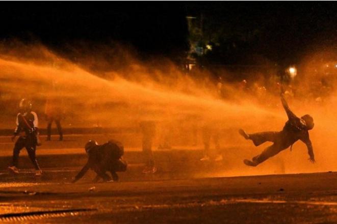 Un manifestant touché par un canon à eau à Bogotá, Colombie, le 12juin 2021 © Juan Barreto
